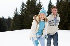 Junge Paare in der alpinen Schnee-Szene Stockfoto