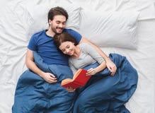 Junge Paare in der Draufsichtmorgenkonzept-Lesegeschichte des Betts stockfotografie