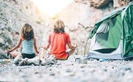 Junge Paare der Gesundheit, die Yoga nahe bei Feuer beim Kampieren mit Zelt auf einem Berg - Freunde zusammen meditieren auf Fels stockfoto