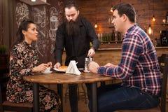 Junge Paare der Kellnerumh?llung mit H?rnchen in der Weinlesekaffeestube stockbilder