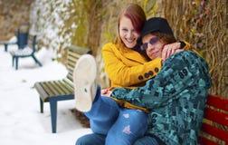 Junge Paare der Liebe, die auf der Bank sitzen Lizenzfreie Stockfotografie