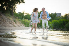 Junge Paare in der Liebe, die durch die Wasservorrathände läuft Lizenzfreie Stockfotos