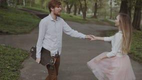 Junge Paare in der Liebe, die in Sommer geht, parken Händchenhalten Frau im rosa Ballettröckchenrockmann mit longboard in Händen  stock video footage