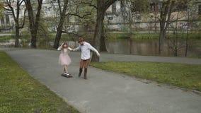 Junge Paare in der Liebe, die in Sommer geht, parken Händchenhalten Frau im rosa Ballettröckchenrockmann mit longboard in Händen  stock video