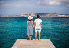 Junge Paare in der Liebe genießen schöne Seelandschaft auf Pier in ihm lizenzfreies stockbild