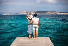 Junge Paare in der Liebe genießen schöne Seelandschaft auf Pier in ihm stockfoto