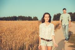 Junge Paare in der Liebe im Freien Paarläufe über dem Feld lizenzfreie stockbilder