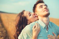 Junge Paare in der Liebe im Freien Verbinden Sie das Umarmen Junge schöne Paare in der Liebe, die auf dem Feld auf Sonnenuntergan lizenzfreies stockbild