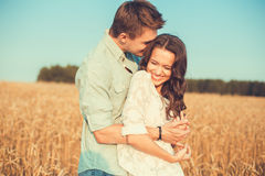 Junge Paare in der Liebe im Freien Verbinden Sie das Umarmen Junge schöne Paare in der Liebe, die auf dem Feld auf Sonnenuntergan lizenzfreies stockfoto