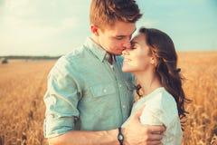 Junge Paare in der Liebe im Freien Verbinden Sie das Umarmen Junge schöne Paare in der Liebe, die auf dem Feld auf Sonnenuntergan stockbild