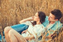 Junge Paare in der Liebe im Freien Verbinden Sie das Umarmen Junge schöne Paare in der Liebe, die auf dem Feld auf Sonnenuntergan Lizenzfreie Stockfotografie
