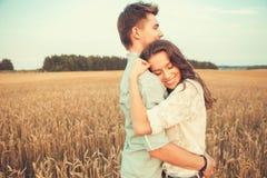 Junge Paare in der Liebe im Freien Verbinden Sie das Umarmen Junge schöne Paare in der Liebe, die auf dem Feld auf Sonnenuntergan stockfotografie