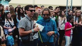 Junge Paare in der Sonnenbrille bleiben im Park unter anderen Besuchern Sommerfestival stock video footage