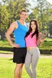 Junge Paare in der Sportkleidung, die im Park aufwirft Lizenzfreies Stockfoto