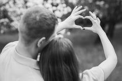 Junge Paare des Mannes und der Frau, die Herzen von den Händen machen Stockbild