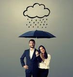 Junge Paare des smiley mit schwarzem Regenschirm Lizenzfreies Stockfoto