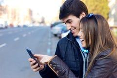 Junge Paare des Touristen in der Stadt unter Verwendung des Handys Stockfotos