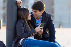 Junge Paare des Touristen in der Stadt unter Verwendung des Handys Stockbild