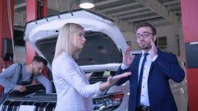 Junge Paare, die über defektem Automobil mit offener Haube streiten, die Selbsttechniker in der Tankstelle repariert stock footage