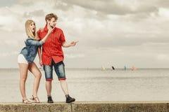 Junge Paare, die überraschte Vertretung mit dem Finger schauen Stockbild