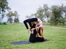 Junge Paare, die acro Vogel-Yogahaltung tun Moderne Tätigkeit des gesunden Lebensstils Stockfoto