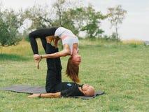 Junge Paare, die acro Vogel-Yogahaltung tun Moderne Tätigkeit des gesunden Lebensstils Stockbild
