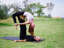 Junge Paare, die acro Vogel-Yogahaltung tun Moderne Tätigkeit des gesunden Lebensstils Lizenzfreies Stockfoto