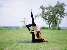 Junge Paare, die acro Vogel-Yogahaltung tun Moderne Tätigkeit des gesunden Lebensstils Stockfotos