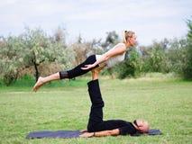 Junge Paare, die acro Vogel-Yogahaltung tun Moderne Tätigkeit des gesunden Lebensstils Lizenzfreies Stockbild