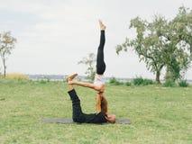 Junge Paare, die acro Vogel-Yogahaltung tun Moderne Tätigkeit des gesunden Lebensstils Lizenzfreie Stockfotos