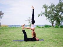 Junge Paare, die acro Vogel-Yogahaltung tun Moderne Tätigkeit des gesunden Lebensstils Stockbilder