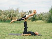 Junge Paare, die acro Vogel-Yogahaltung tun Moderne Tätigkeit des gesunden Lebensstils Lizenzfreie Stockbilder