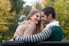 Junge Paare, die auf Bank sitzen Stockfotos