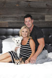 Junge Paare, die auf Bett sitzen Lizenzfreies Stockbild
