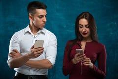 Junge Paare, die auf blauem Hintergrund aufwerfen Lizenzfreies Stockbild