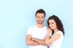 Junge Paare, die auf blauem Hintergrund stehen Lizenzfreie Stockfotos