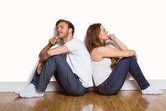 Junge Paare, die auf Boden sitzen Lizenzfreie Stockbilder