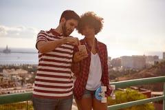 Junge Paare, die auf Brückengeländer sich lehnen lizenzfreie stockbilder