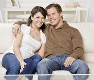 Junge Paare, die auf Couch umarmen Stockbilder
