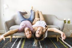 Junge Paare, die auf das Sofa mit den Köpfen umgedreht legen lizenzfreie stockfotografie