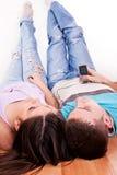 Junge Paare, die auf dem Fußboden liegen Stockbild