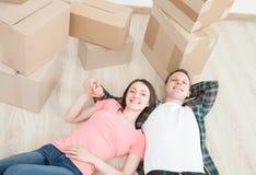 Junge Paare, die auf dem Fußboden liegen Lizenzfreies Stockfoto