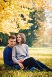 Junge Paare, die auf dem Gras sitzen stockbild