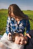Junge Paare, die auf dem Gras sitzen Junge setzte seinen Kopf zu Mädchen ` s Knien Lizenzfreie Stockfotografie