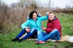 Junge Paare, die auf dem Plaid und dem Getränkkaffee von einem Thermo sitzen lizenzfreies stockbild