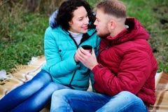 Junge Paare, die auf dem Plaid und dem Getränkkaffee von einem Thermo sitzen lizenzfreie stockfotografie