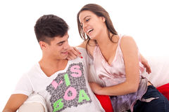 Junge Paare, die auf dem Sofa sich entspannen Lizenzfreie Stockfotografie