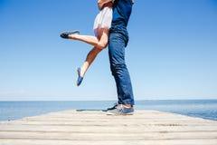 Junge Paare, die auf dem Strand küssen Stockfotografie