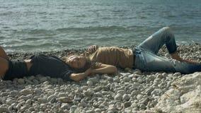 Junge Paare, die auf dem Strand liegen stock footage