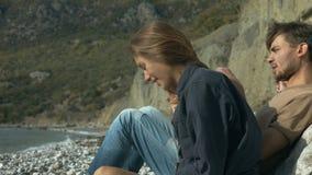 Junge Paare, die auf dem Strand sitzen und umarmen stock footage